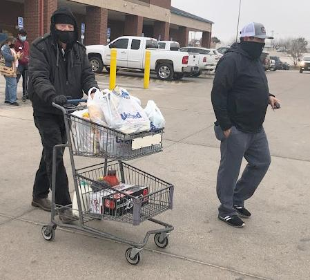 United Supermarkets employee Clyde Wallace (left) and customer Patrick Alderete bundled up against the cold while walking groceries out to Alderete's car.