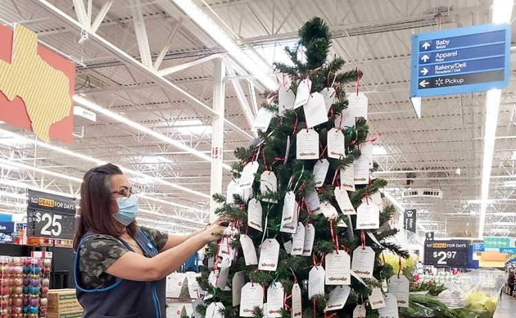 Wal-Mart Team Lead Dora Little hangs cardstock ornaments ­— each bearing age, sizes and Christmas wishes of a child served by the West Texas Children's Advocacy Center — on the Angel Tree at Wal-Mart.